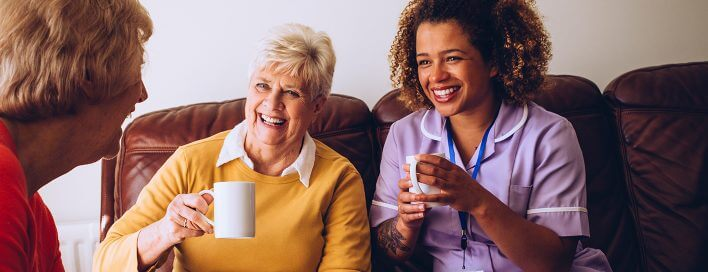 Nurse laughing with elderly people
